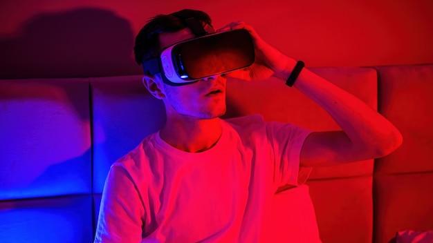 ベッドの部屋に青と赤のイルミネーションを備えたバーチャルリアリティグラスの若い印象的な男。自宅でのエンターテインメント