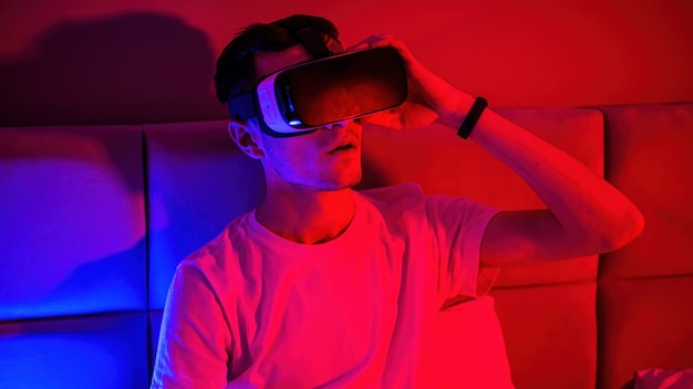 Young impressed man in virtual reality glasses with blue and red illumination in the room in the bed. entertainment at home
