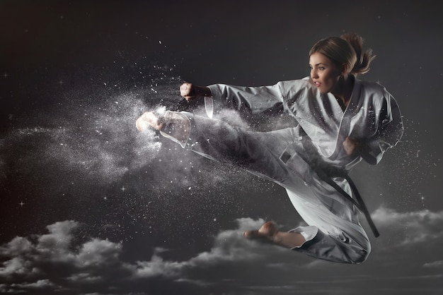 Young impudent emotional karate girl in a suit jumps up and makes a powerful blow. unrestrained energy concept. martial arts