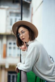 透明なメガネと帽子のバルコニーに滞在の若い