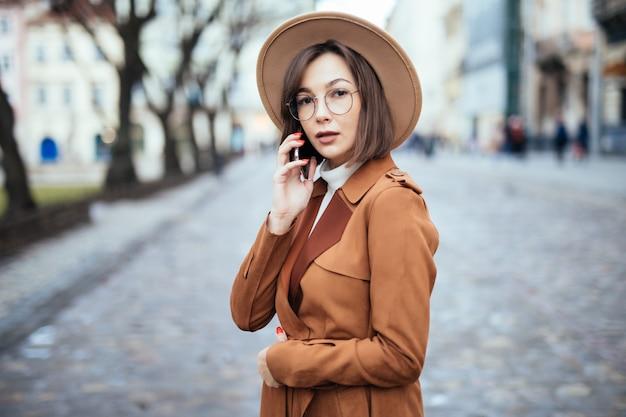 スマートフォンで話す広い帽子の若い秋のストリート