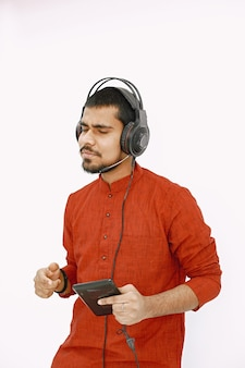 Young indaian guy in headphones listening to music. dancing on white wall, isolated.
