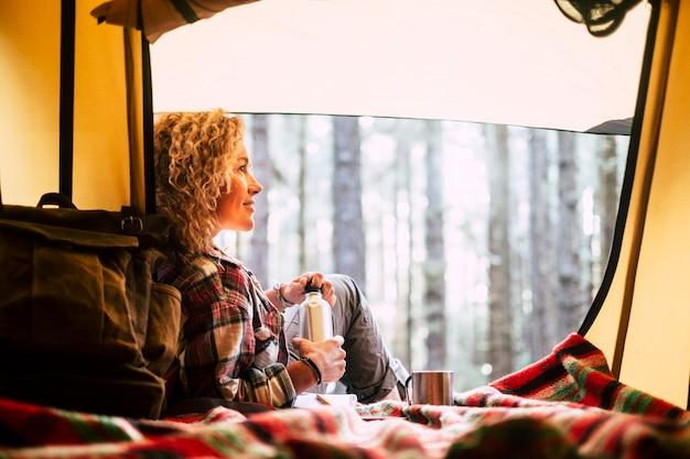 若い独立した女性は、美しい森の自然の景色を眺めながらテントの中で楽しんでいます