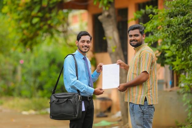 若いインドの銀行員が書類を完成させ、農民に証明書を渡します。