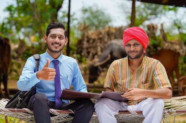 彼の農場で農夫と紙の仕事を完了する若いインドの銀行役員。