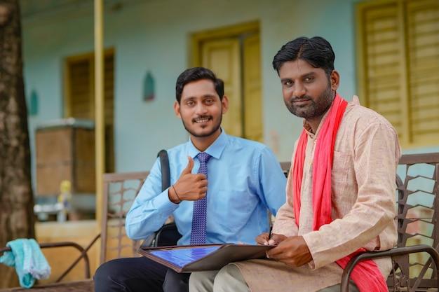 彼の家で農夫と紙の仕事を完了する若いインドの銀行役員。