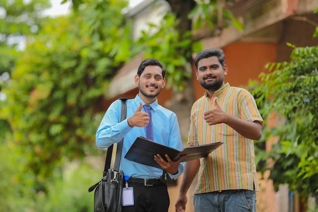 農民との事務処理を完了する若いインドの銀行役員。