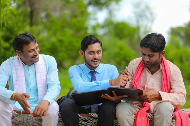 自宅で農民と紙の仕事を完了する若いインドの銀行役員。