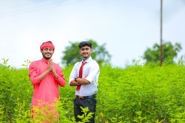 グリーンフィールドの若いインドの農学者と農民
