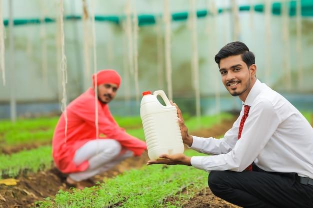 温室でボトルを見せている若いインドの農学者と農民