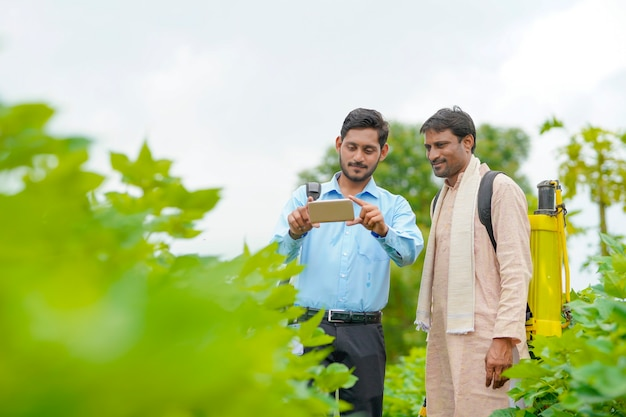 Young indian agronomist or banker showing some information to farmer in smartphone at agriculture field.