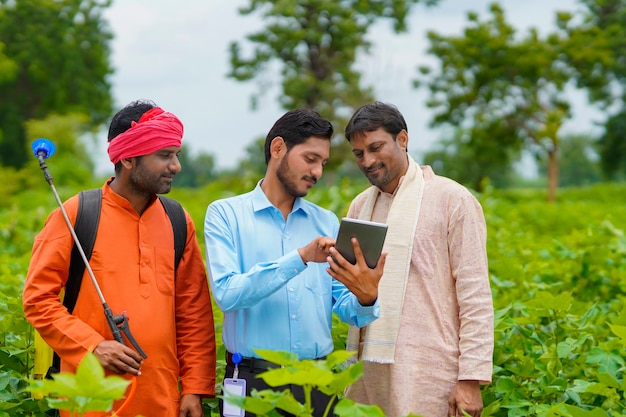 Young indian agronomist or banker showing some information to farmer in tablet at agriculture field.