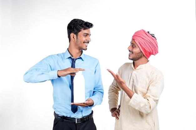 흰색 바탕에 농부에게 병을 주는 젊은 인도 농업 경제학자.