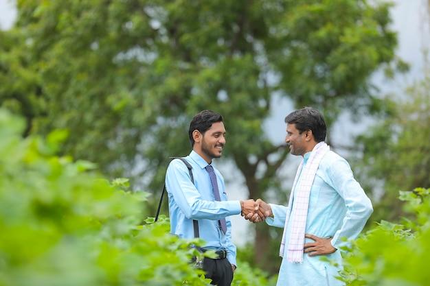 Молодой индийский агроном или банкир пожимает руку фермеру на сельскохозяйственном поле.