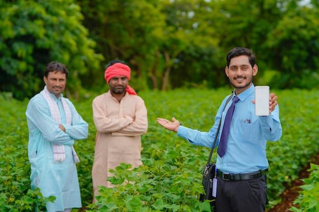 農業分野で農民とスマートフォンを見せている若いインドの農学者または銀行家。