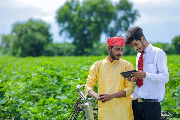 スマートフォンで農家にいくつかの情報を示す若いインドの農学者または銀行家