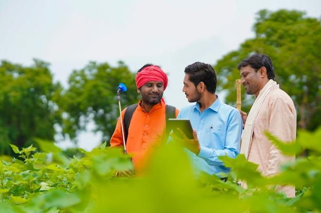 젊은 인도 경제학자나 은행가는 농업 분야에서 태블릿으로 농부에게 일부 정보를 보여줍니다.