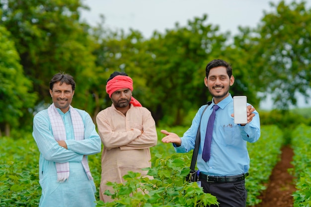 若いインドの農学者または銀行家が農業分野で農民とタブレットを見せています。