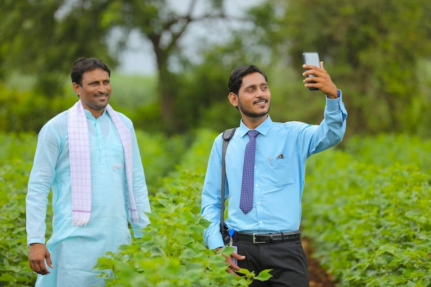 농업 분야에서 농부와 셀카를 찍는 젊은 인도 농업 경제학자 또는 은행가