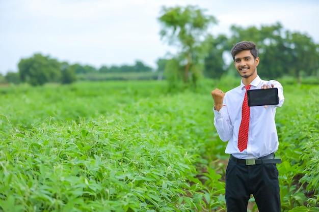Молодой индийский агроном показывает смартфон в поле