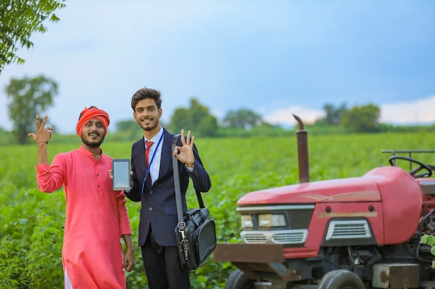 Young indian agronomist showing smartphone with farmer