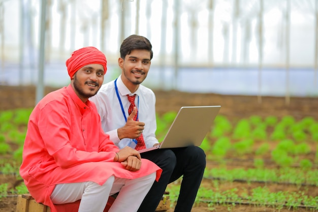 Young indian agronomist showing some information to farmer in laptop at greenhouse