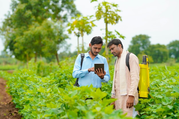 Young indian agronomist showing some information to farmer in tablet at agriculture field.