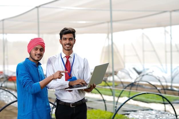 温室でラップトップで農民にいくつかの情報を示す若いインドの農学者