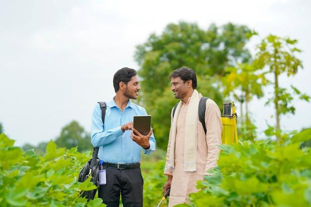농업 분야에서 태블릿으로 농부에게 일부 정보를 보여주는 젊은 인도 농업 경제학자.