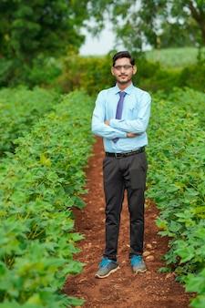 농업 분야에 서 있는 젊은 인도 농업 경제학자.