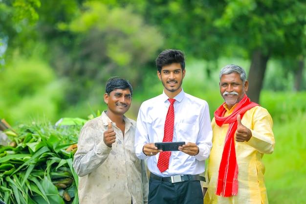 農業分野で農民と携帯電話でいくつかの情報を示す若いインドの農学者