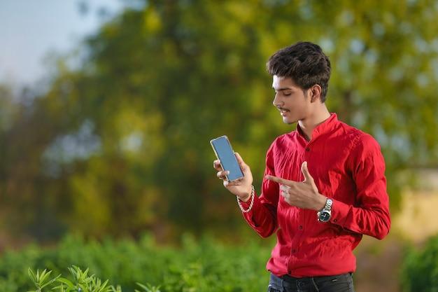 スマートフォンを持つ若いインドの農学者
