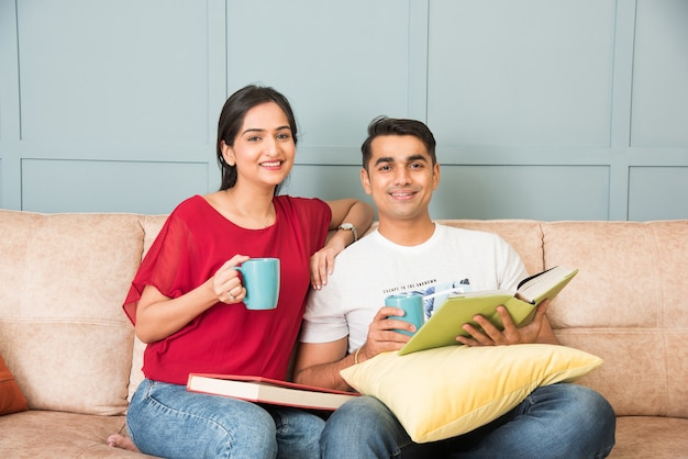 Young indian asian couple reading books while sitting on sofa at home, modern living space