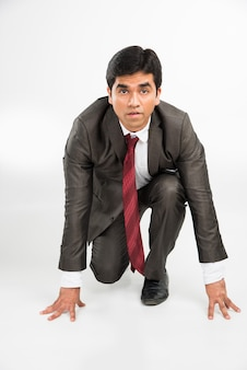 Young indian asian smart and determined businessman running or standing in start position, isolated over white
