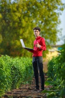 Молодой индийский руководитель банка, стоя на поле с ноутбуком