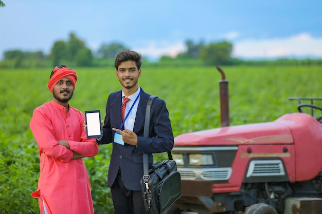 Young indian bank officer and farmer showing smartphone at agriculture field