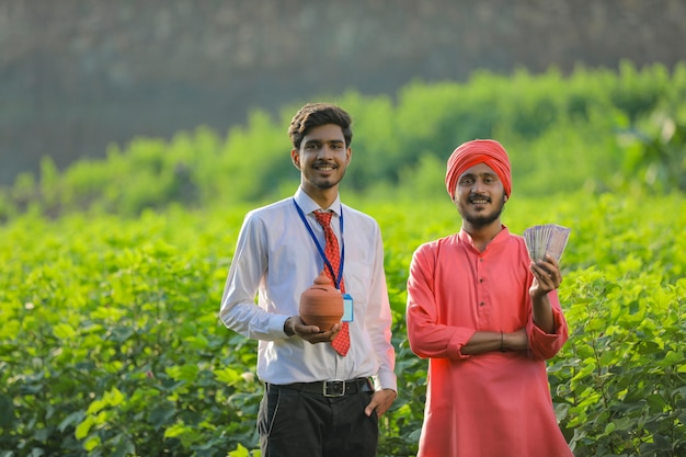 Young indian banker or agronomist and farmer showing money and clay piggy bank at field