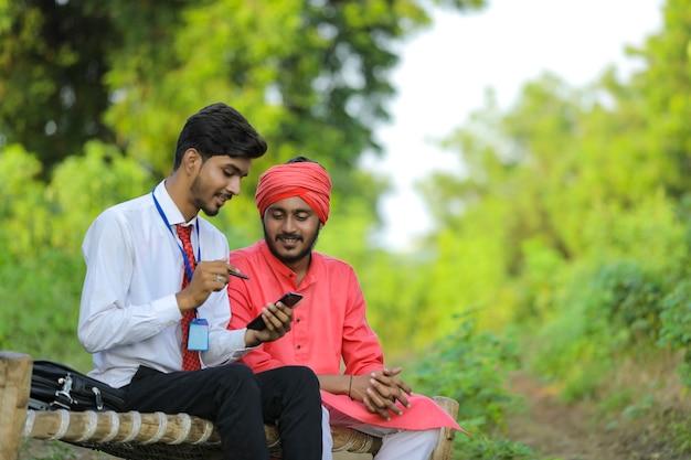 若いインドの銀行家が畑で農民と話し合う