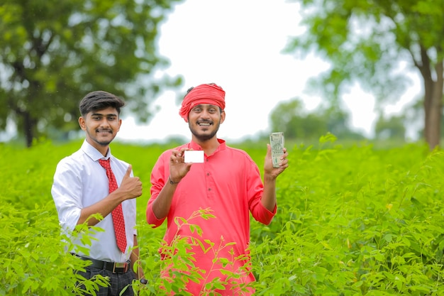 Young indian banker and farmer showing card at green field