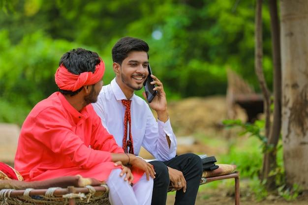 携帯電話で話している若いインドの銀行家または農学者