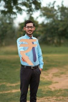 手にルピー記号を保持している若いインドの銀行家または金融業者