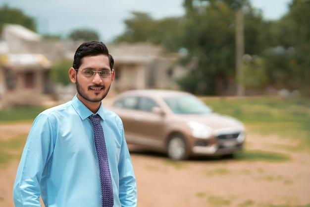 車で立っている若いインドの銀行家または金融業者