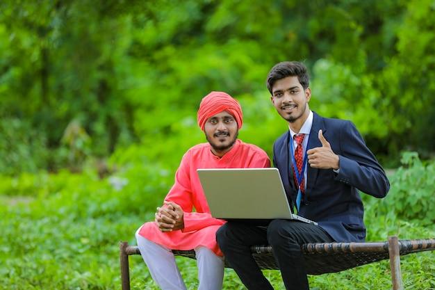 Молодой индийский банкир показывает некоторую информацию фермеру в ноутбуке на поле