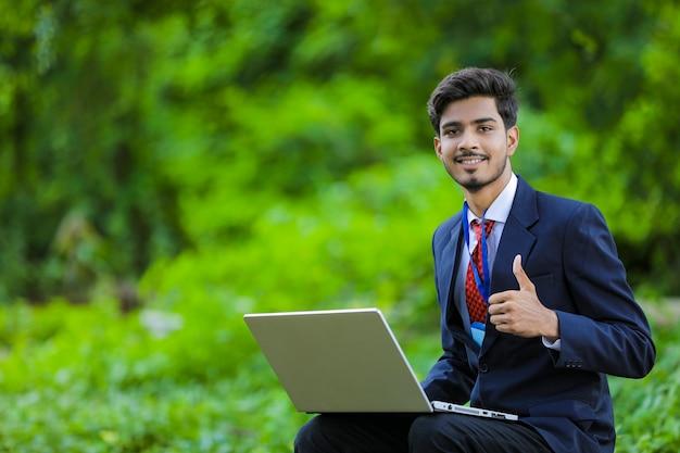 フィールドでラップトップを使用して若いインドの銀行家