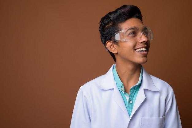茶色の背景に保護眼鏡をかけている若いインド少年医師