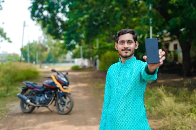 민족 착용 및 스마트 폰 보여주는 젊은 인도 소년