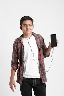 Young indian boy listening music and using smartphone on white wall