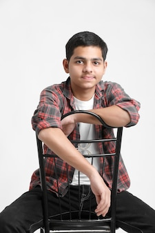 Young indian boy sitting on chair and showing expression on white wall