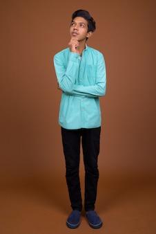 茶色に対してスマート探している青いシャツを着ている若いインドの少年