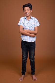 茶色の背景に市松模様のシャツを着ている若いインド少年